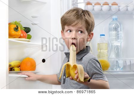 Little boy eating banana near open fridge