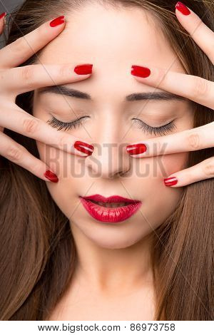 Portrait Of Attractive Young Female With Red Nail Polish, On Dark Background
