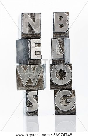 the words news and blog written with lead letters an old printing press,