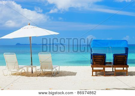 Beach chairs at beautiful tropical beach with white sand, turquoise ocean water and blue sky at exotic island