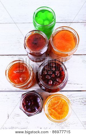 Homemade jars of fruits jam on color wooden planks background