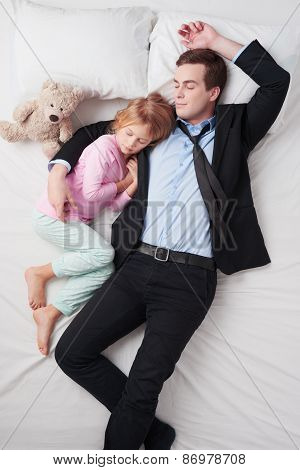 Top view of tired businessman and his sleeping little daughter