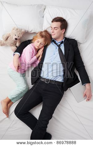 Top view of businessman and his sleeping little daughter