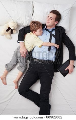 Top view of businessman and his little sleeping son