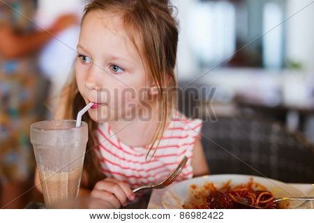 Portrait of adorable little girl having  lunch at restaurant