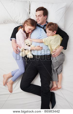 Top view of tired businessman and his two children