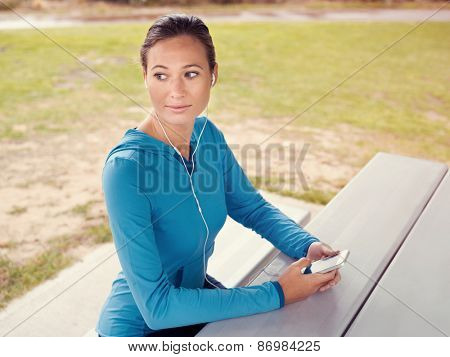 Sporty young woman with a phone and earphones