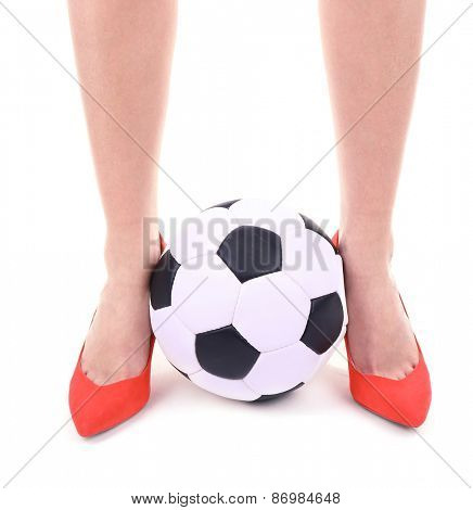 Female legs in red shoes with soccer ball isolated on white