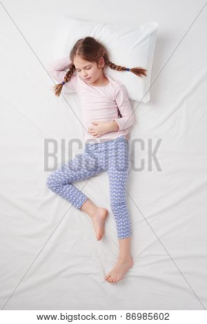 Top view of little cute girl with pigtails sleeping