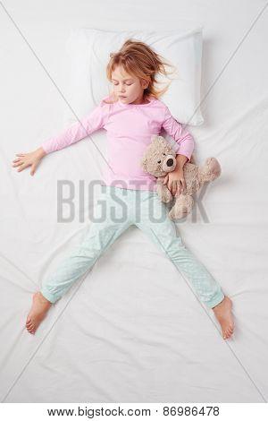 Top view of little girl sleeping in Freefaller pose