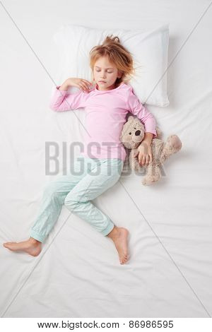 Top view of little girl sleeping with teddy bear