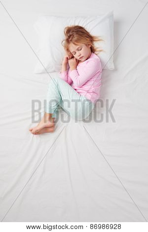 Top view of little girl sleeping in Foetus pose