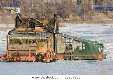 Burnt Wooden Structure Standing On Ice Of River