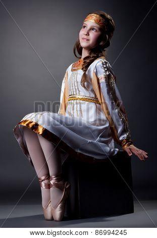 Dreamy little ballerina posing in folk dress