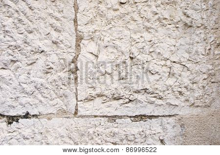 Old beige textured wall with cracks