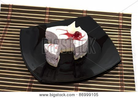 The Made An Incision White Cake, On A Black Plate, On A Rug