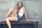 foto of scandinavian  - Scandinavian and nordic urban fashion girl sitting on a bench outdoor in the city - JPG