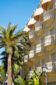 picture of beachfront  - A hotel at the beachfront with some palm trees - JPG
