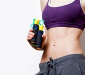 image of jump rope  - Woman showing her abs with jumping - JPG