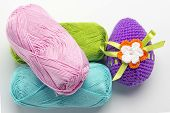 image of boll  - Easter egg made of multicolored crochet yarn on a white background with bolls skeins and crochet hooks - JPG