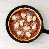 picture of salami  - Raw round pizza with salami onion mozarella in cast iron skillet top view - JPG