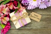 stock photo of bowing  - Border of flowers with gift box and Happy Mother - JPG