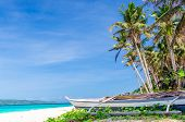 stock photo of boracay  - Tropical beach view and lonely sailboat near palm trees against background of turquoise sea and blue sky at exotic white sandy Puka beach on Boracay island Philippines - JPG