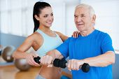 picture of physical therapist  - Confident female physical therapist helping senior man with fitness in health club - JPG