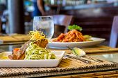 foto of salmon steak  - grilled salmon steak served with pasta and vegetables in a small outdoor restaurant - JPG