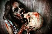 stock photo of bloody  - Frightening bloody zombie girl with a skull - JPG