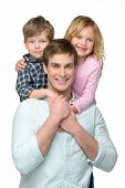 stock photo of piggyback ride  - Cheerful smiling young father with his two kids - JPG