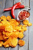 stock photo of potato chips  - Delicious potato chips with sauce on wooden table close - JPG