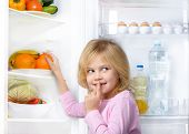 stock photo of silence  - Little cute girl making silence sign and picking food from fridge - JPG