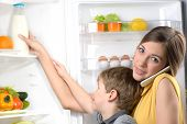 picture of refrigerator  - Young beautiful mother helping her little son to pick bottle of milk from fridge while using phone - JPG