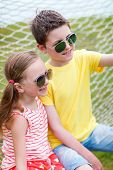 image of sisters  - Teenage boy taking selfie with his little sister outdoors on summer day - JPG
