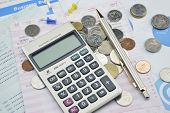 picture of accounting  - Calculator pen pin and coin on saving book accounting background - JPG