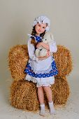 image of girl toy  - Girl in dress standing near a rustic vintage hay with a toy - JPG