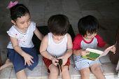 stock photo of happy kids  - Three kids reading book - JPG
