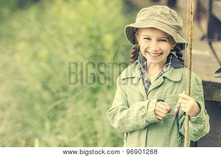 little fisher girl smiles holding a rod