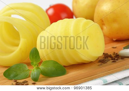 detail of raw potatoes and peel spiral on wooden cutting board