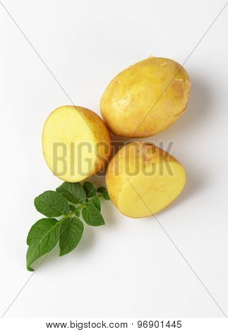 one and two halves baby potatoes with leaves on white background