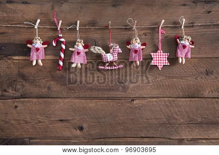 Country style christmas handmade decoration hanging on an old rustic brown wooden background.