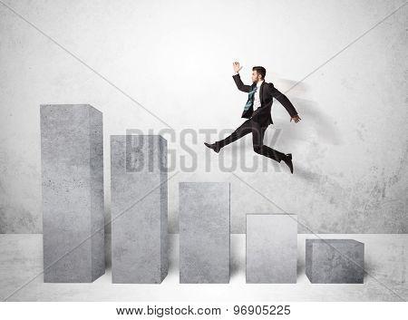 Successful business man jumping over charts on background concept