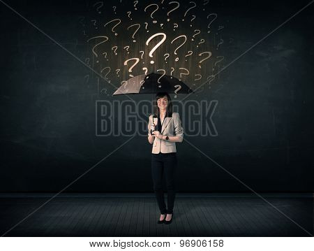 Businesswoman with umbrella and a lot of drawn question marks concept on background