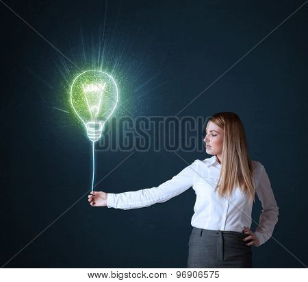Businesswoman hold a shining idea bulb on a blue background