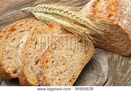 fresh bread and wheat on wooden background
