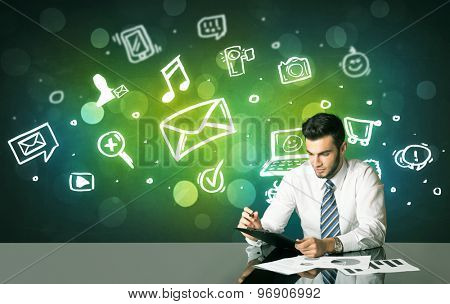 Businessman sitting at the black table with social media symbols on the background