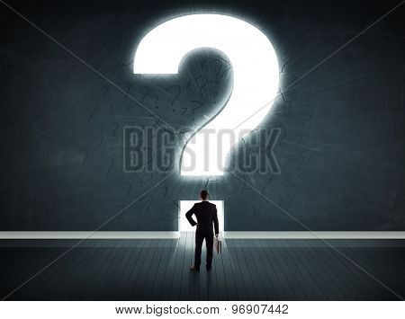 Business man looking at wall with a bright question mark concept