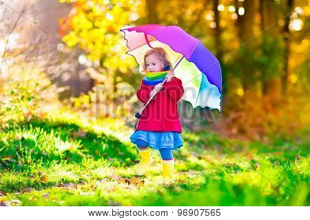 Child Playing In The Rain With Umbrella In Autumn Park