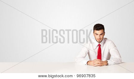 Business man sitting at white table with a white background